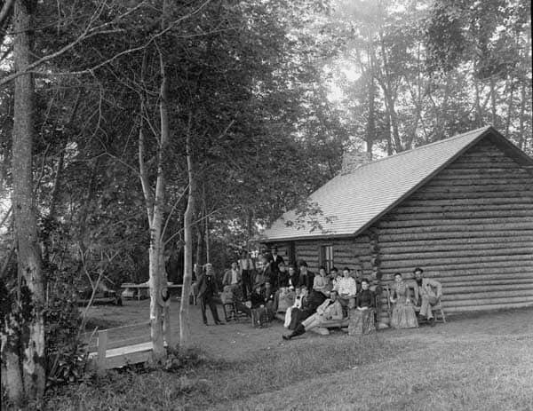 Camp-Comfort-Men-and-women-in-front-of-the-log-cabin-camp_George-Taylor-Photo-PANB