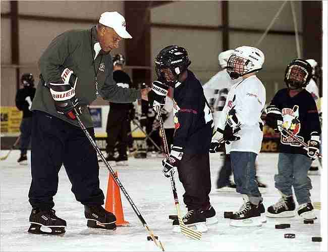 Willie O'Ree instructing young hockey players