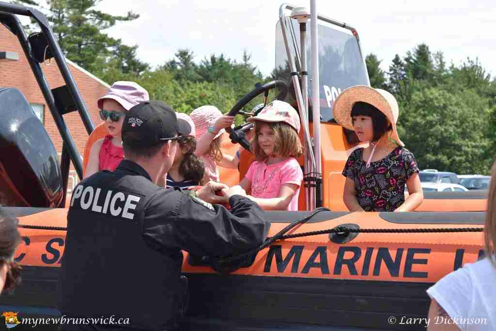 Fredericton police officer shows children the department boat at First Responders Open House